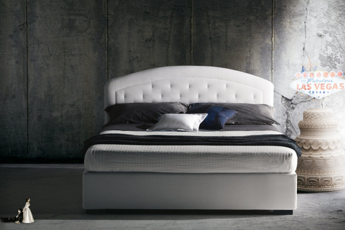 Upholstered bed with rounded tufted headboard