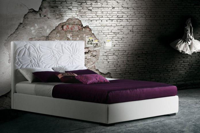 Upholstered bed with floral headboard in plain colours