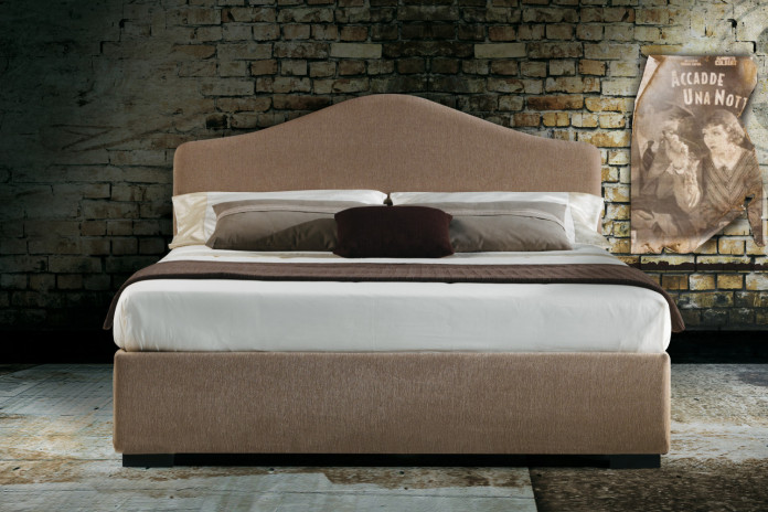 Cottage style upholstered bed with a curved camel back headboard