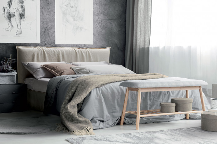 French seam upholstered bed with skirted frame and flanged edge slipcover