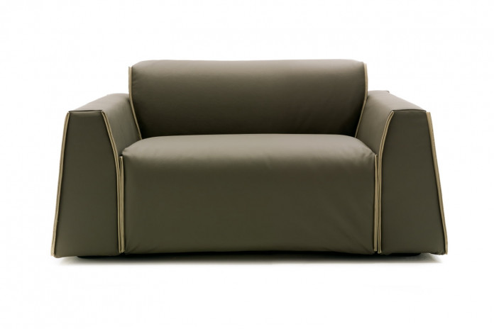 Contemporary low back armchair or snuggle chair with wide seat and wedge arms